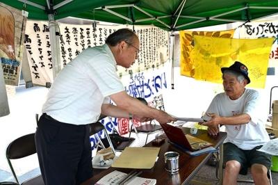 九電前広場で県赤旗まつりの案内をする岡野隆県委員長